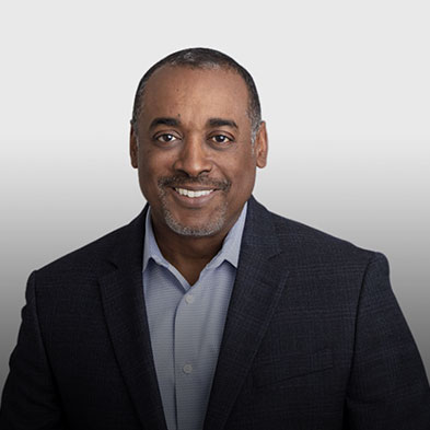 Picture of Darrell Winfield, Chief Information Officer at Paya. He has short black hair, a black and gray goattee, is smiling proudly at the camera, and is clad in a black sports coat with a light blue shirt underneath.