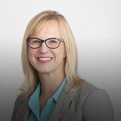 Picture of Paya's head of Product, Marketing, & Communications, Andrea Kando. She is smiling, has blond hair, and is clad in a dark gray blazer with a light blue undershirt.