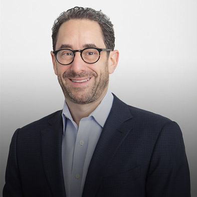 Top half shot of Paya's CEO Jeff Hack smiling at the camera. He has short, curly hair, a short beard, glasses and is clad in a blazer with a blue undershirt.