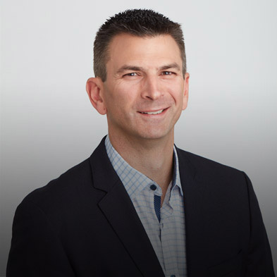 Top half shot of Paya's Chief Revenue Officer Mark Engels smiling at the camera. He is a tall, short-haired man clad in a blazer with a blue undershirt.